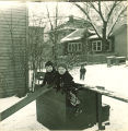 Small boys playing on a slide in the snow, The University of Iowa, January 1938
