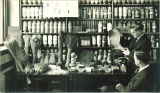 Examining dry goods in the commercial museum in University Hall, the University of Iowa, 1928