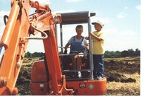 Woman and young boy on backhoe