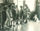 Line of small children in a playroom, The University of Iowa, 1920s
