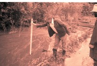 Man Measures Depth of Water in Flooded Area