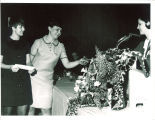 Scottish Highlanders lead dancer Bonnie Luzius and lead drummer Marcia Nice receiving Adamson-Highlander scholarship from drum major Kathy Monahan, The University of Iowa, ca. 1968