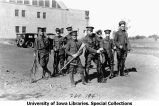 Cadets standing at ease with rifles next to Armory, The University of Iowa, 1922