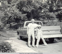 Bill and John, Jr. wearing a hat, leaning on truck