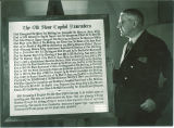 "Benjamin Shambaugh standing next to a plaque called ""Old Stone Capitol Remembers"" in Old Capitol, The University of Iowa, March 1944"