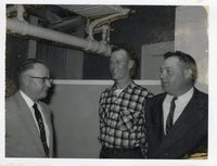 Three Unidentified Men Stand Facing Each Other with Pipes Overhead