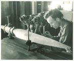 Engineering student measuring propeller in engineering laboratory, The University of Iowa, 1939