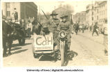 Soldiers riding motorcycle and sidecar in Mecca Day parade, The University of Iowa, 1918