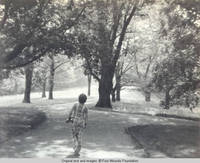 John, Jr. walks down the lane at intersection with service lane by Grey house