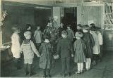 School children around Christmas tree, The University of Iowa elementary school, 1920s