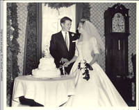 Frindy and John, Sr. cutting the wedding cake, facing each other, in dining room