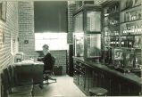 Woman working at desk in pharmacy laboratory, The University of Iowa, 1930s
