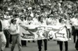 The ISU Alumni Band marching behind their banner at Homecoming, 1985