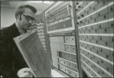 Professor checking front panel of equipment, 1970