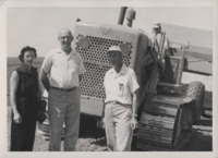 Harold Shold, Bill Beddow, and Lois Beddow pose in front of a tractor.