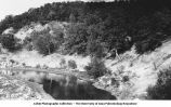 Coal Measure Shale (middle of picture) resting in eroded channel in St. Louis sandstone (seen in lower corners of picture) on Cedar Creek, Bellefontaine, Iowa, late 1890s or early 1900s.