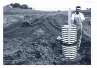 Clyde Small stands beside inlet of pipe spillway of his pond under construction, 1966
