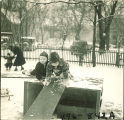 Children playing on wooden planks in snow, The University of Iowa, February 22, 1938