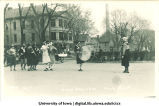 Marching band with men in women's attire, Mecca Day parade, The University of Iowa, 1921