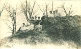 Women sitting on large haystack, Iowa, March 12, 1908