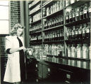 Pharmacy student filling medicine bottle, The University of Iowa, 1940s