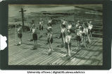 Students participating in canoe stroke practice and track and field events, The University of Iowa, 1930s