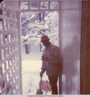 Ainsley Benard sweeping snow off the steps of White house with Victoria, the dog