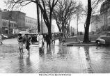 Pedestrians in the rain on Washington St., Iowa City, Iowa, between 1945 and 1950