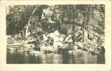 Man fishing and people watching while sitting on rocks, Fayette, Iowa, August 23, 1919