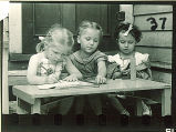 Girls writing and playing at a table outside, The University of Iowa, May 10, 1941
