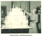 Nell Alderman lighting candles on Centennial Dinner layer cake, Iowa Memorial Union, University of Iowa, February 25, 1947