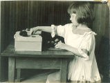 Girl playing at a table, The University of Iowa, ca. 1920