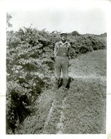 Farmer in overalls and glasses with hands in pockets stands next to shrubs