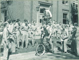 Students performing acrobatic trick on bicycle, The University of Iowa, 1940s