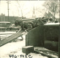 Child playing on wooden plank in snow, The University of Iowa, February 22, 1938