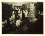 Engineering student adjusting machine in engineering laboratory, The University of Iowa, 1939