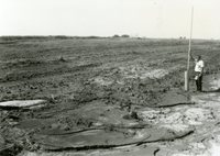 Man Stands by TOT Pipe in Field