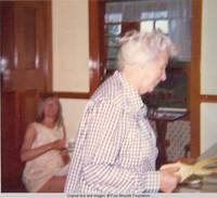 Unknown woman and Elizabeth with tongs in kitchen