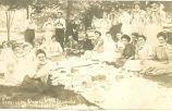 People eating watermelon at Seminary Alumni picnic, Epworth, Iowa, August 4, 1909