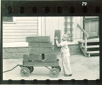 Boy loading a wagon with wood boxes, The University of Iowa, May 10, 1941