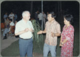Earl O. Heady outside at an evening social event in Thailand talking with a man and a woman, 1983.
