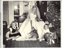 Unknown children sit with John, Sr. and Frindy, who is petting corgies in sun porch