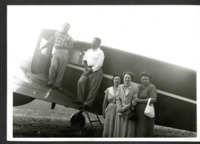 A Group Poses in Front on an Airplane