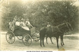 People seated in horse-drawn wagon, Cedar Rapids?, Iowa, 1910s