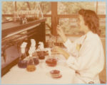 Woman researcher transferring colored fluids between beakers and petri dishes with pipette
