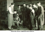 Engineering students watch and listen as their teacher explains a machine, The University of Iowa, 1920s