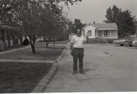 Unidentified Man Stands in Street with Hand Raised