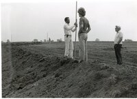 1979 -  William Baugh, Des Moines County soil conservation aid, holds a measuring tool in a field while two men watch