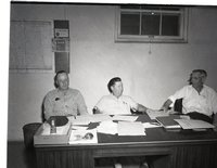 Three Unidentified Men Meet Behind a Desk