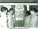 Football team view past newspaper headlines encouraging them to beat Notre Dame again, The University of Iowa, 1960s